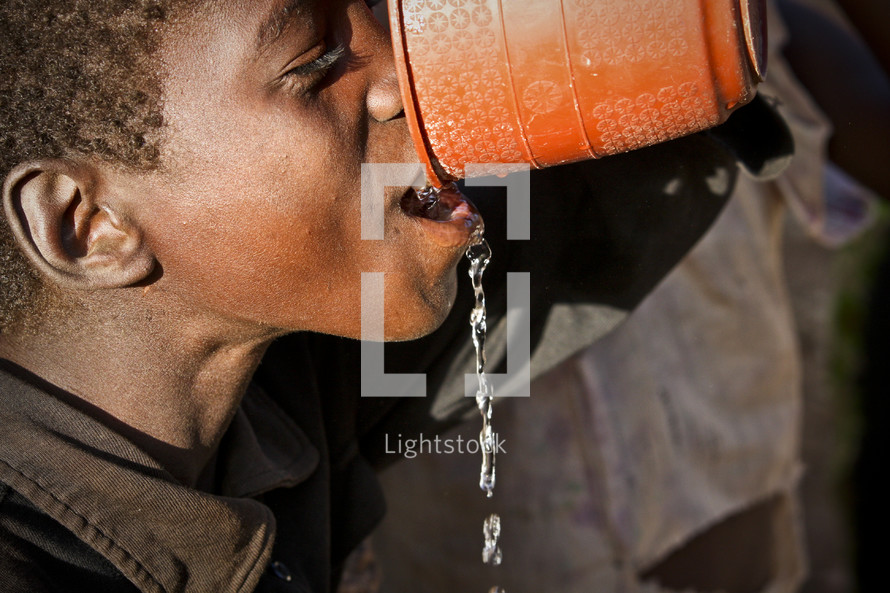Boy drinking water from a bowl