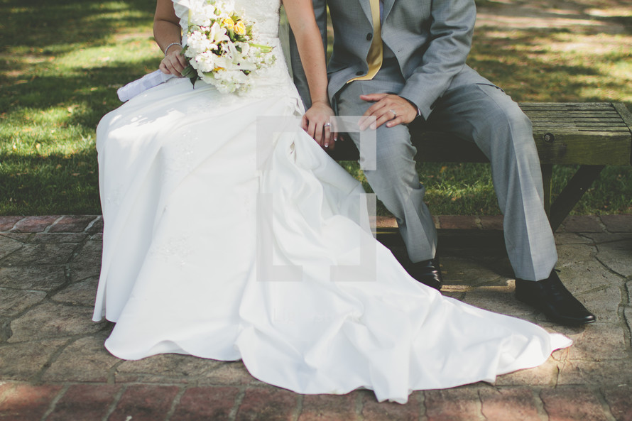 a married couple sitting on a bench and holding hands after their wedding