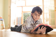 A child lying on the floor and reading the Bible.