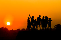 A group of children against a sunset.