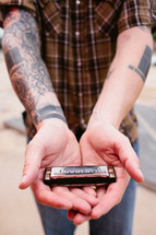 man with tattoos holding a harmonica