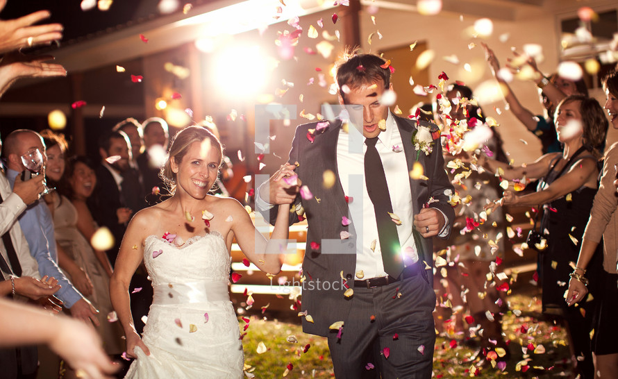 bride and groom under confetti leaving for their honeymoon