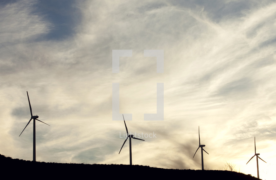Silhouettes of windmills under a cloudy sky