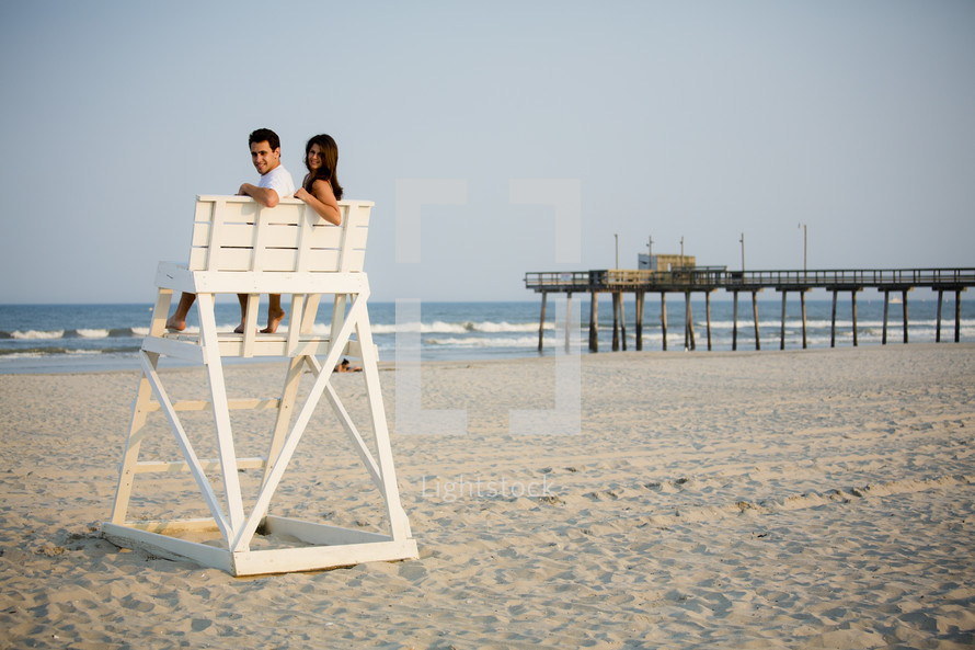 couple sitting together on a lifeguard stand on a beach