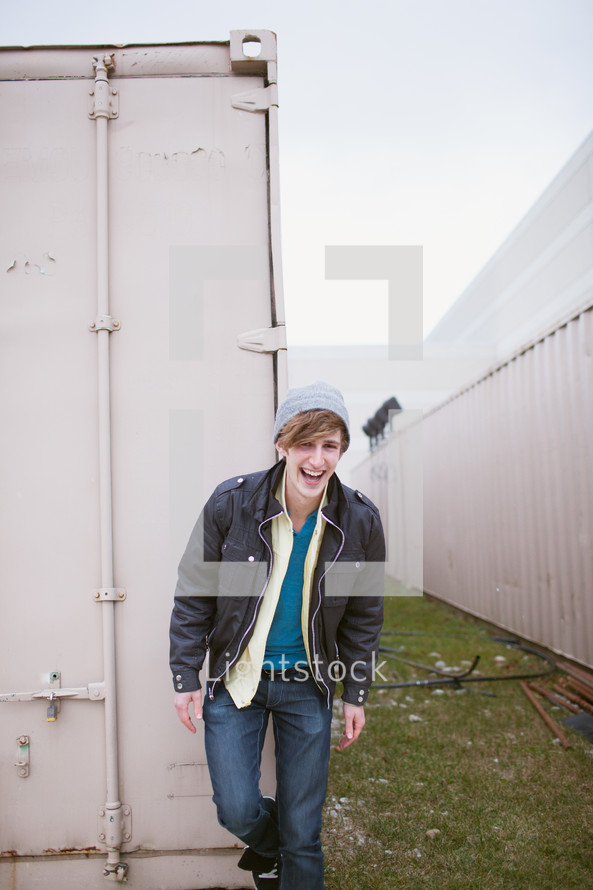 laughing man in a hat and jacket standing in front of a storage bin