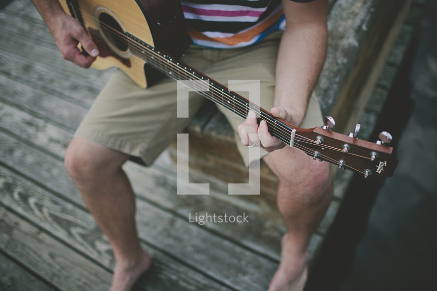 Man playing guitar on the dock