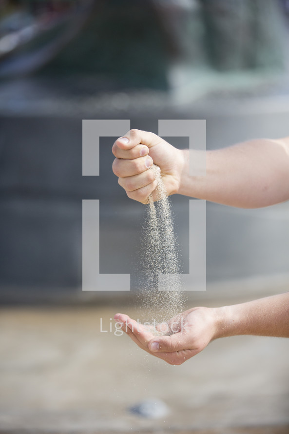 Hands sifting and catching sand