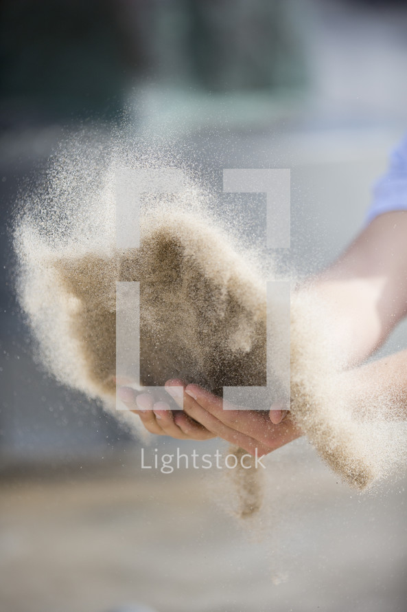 Hands throwing sand