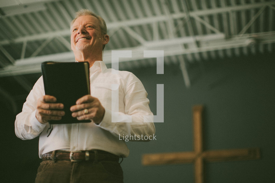 Man holding Bible in front of cross.