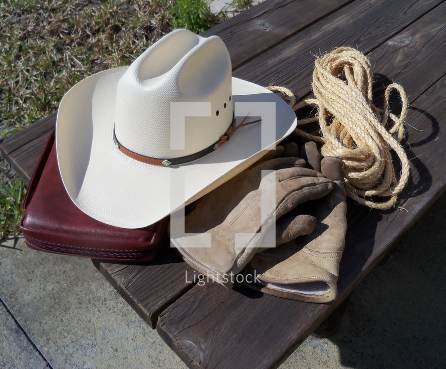 the tools of the trade that a good cowboy cannot do without - A good pair of gloves to do chores, a strong rope for roping cattle, a cowboy hat to shied him from the heat of the sun and the word of God to keep his heart pure.