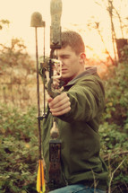 Young man aiming bow and arrow