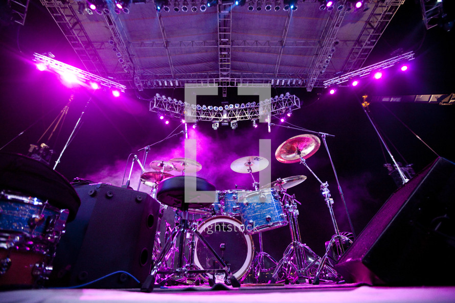 A backstage view of drums on a stage lit by purple lights