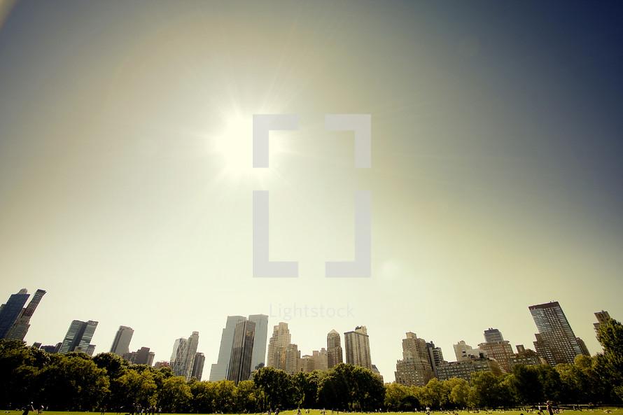 sun in clouds, city skyline,