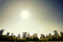 sun in clouds, city skyline,