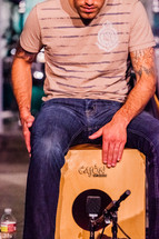 Man sitting on a wooden box playing cajon hands hitting drum percussion