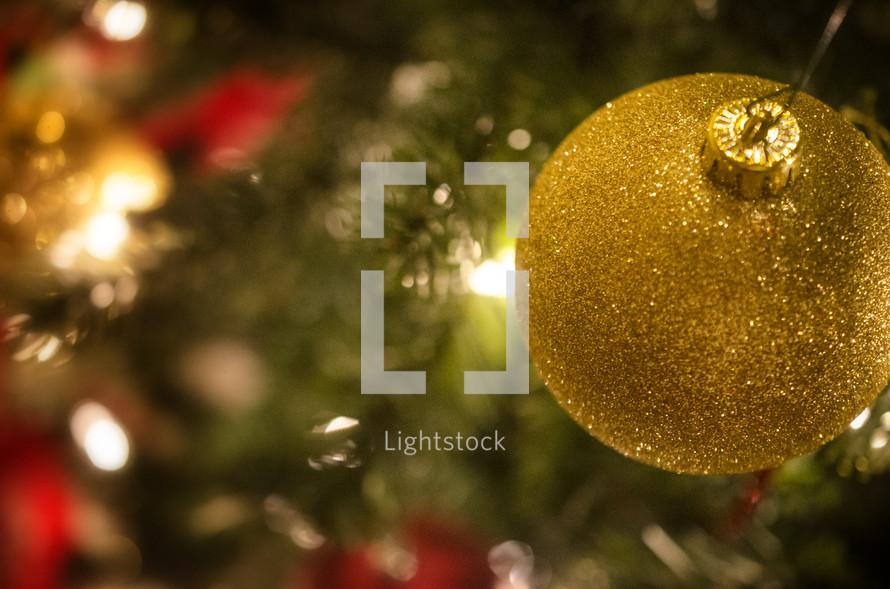 Gold glitter ball ornament hanging on Christmas tree.