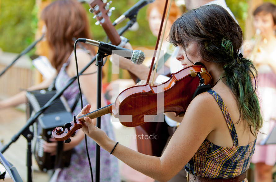 woman in a band playing a violin