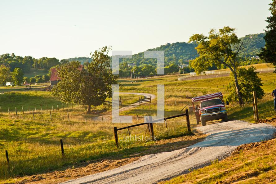 truck driving down a farm dirt road