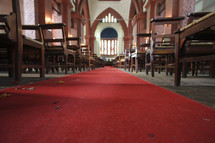 Red carpet running down cathedral aisle lined with wooden pews.