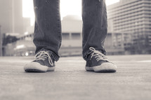 legs in sneakers standing on a city sidewalk