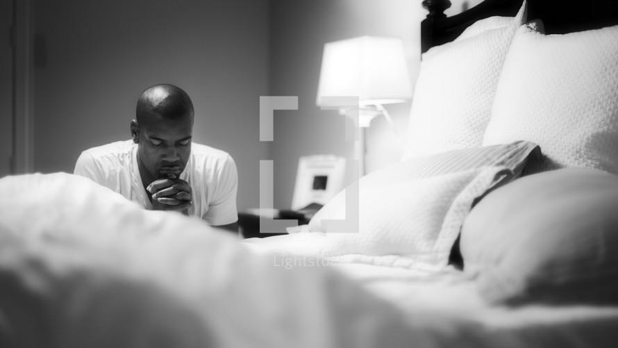 man kneeling in prayer by his bedside