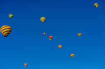 Hot air balloons bright colored in blue sky many multiple.