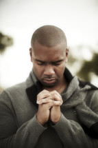 An African American man with head bowed and hands laced in prayer