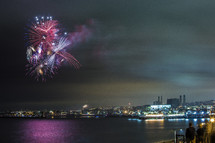 Fireworks over the water by city skyline