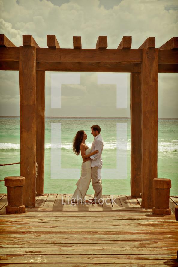 A couple embracing under an arbor near the ocean