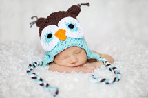 Sleeping infant with owl hat