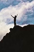 man with arms raised in worship to God on top of a mountain