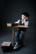 boy child sitting at a desk with his head on his hand in front of a stack of books