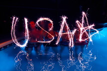 People spelling USA with sparklers. 4th July, independence day celebrations.