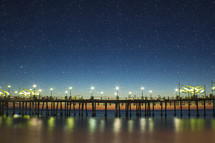 Star filled sky over a pier