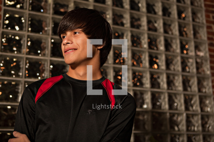 young man standing by glass brick wall