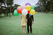 couple holding helium balloons