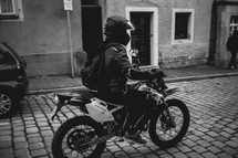 man riding a motorbike on a cobble stone street