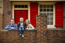 Family posing outside their home.