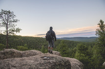 a man standing on a mountaintop at sunrise