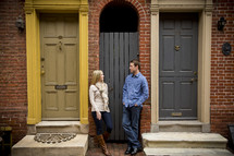 Woman and man standing between two doorways.