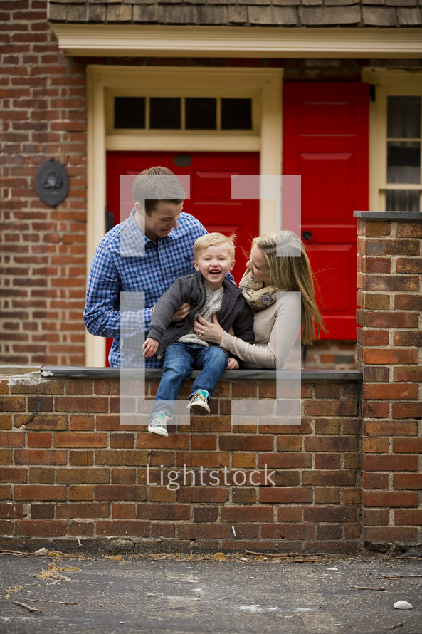 young family looking over a brick fence