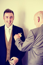 A father placing a boutonniere on his groom son.