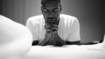 A man kneeling by his bed praying