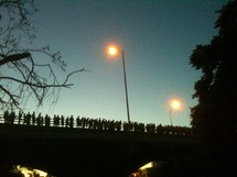 Silhouette of crowd of people standing on bridge with streetlights at dusk.