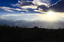 sun peeking through the clouds over a field