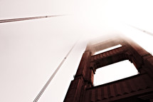 A close up of the Golden Gate Bridge covered in fog