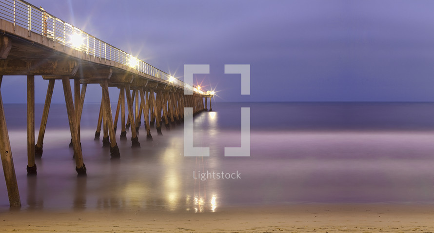 Wooden bridge with lights at dusk
