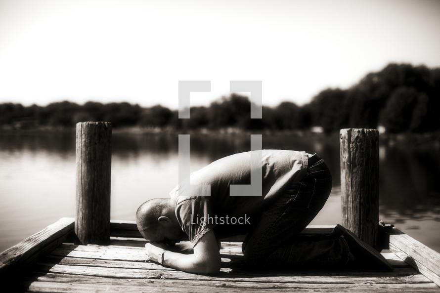 Man kneeling in prayer on river dock