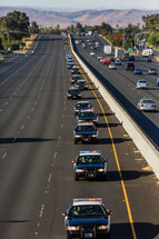 line of police cars on a highway, funeral procession