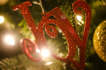 "Red glitter ""Joy"" ornament hanging on Christmas tree."